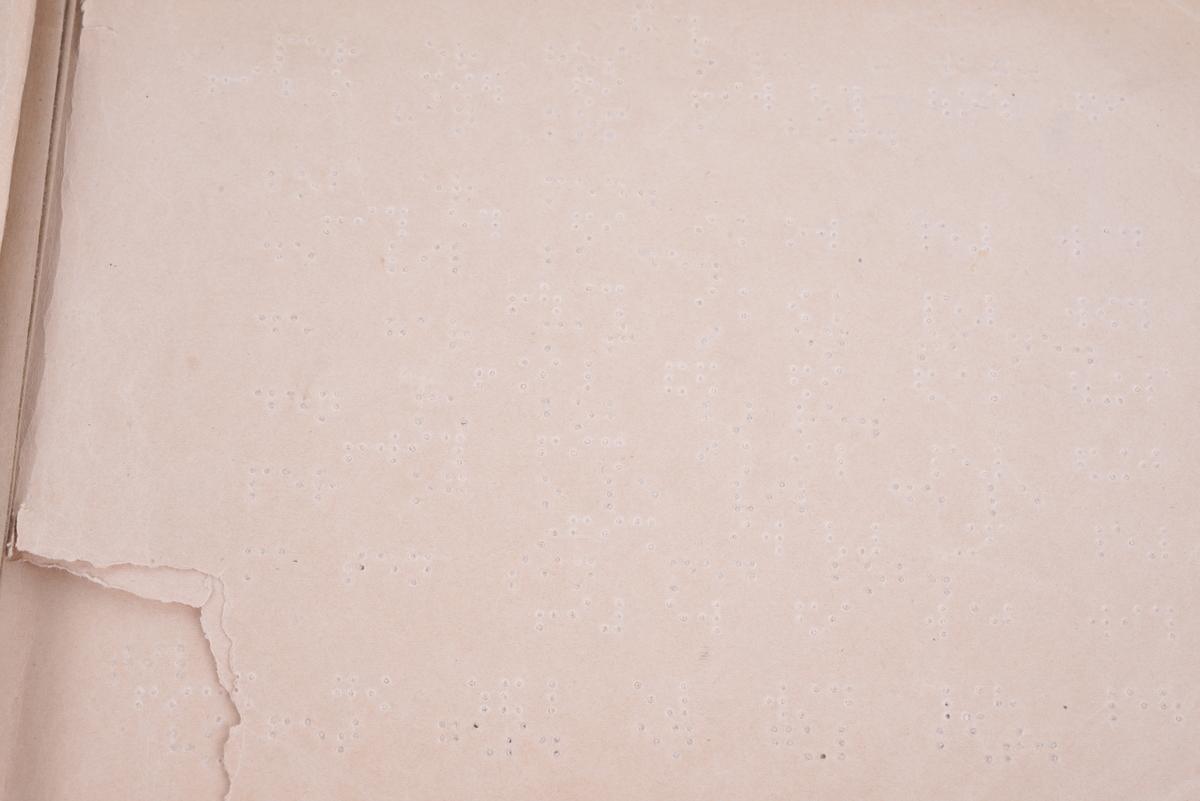 Innbundet bok med punktskrift. Tosidig trykk. Grønt marmorert omslag av papp. Grått tykt papir på forsatsen. Tekstilhalvbind; ryggen og hjørnene er forsterket med grønn tekstil. Brun etikett av papir på bokryggen.