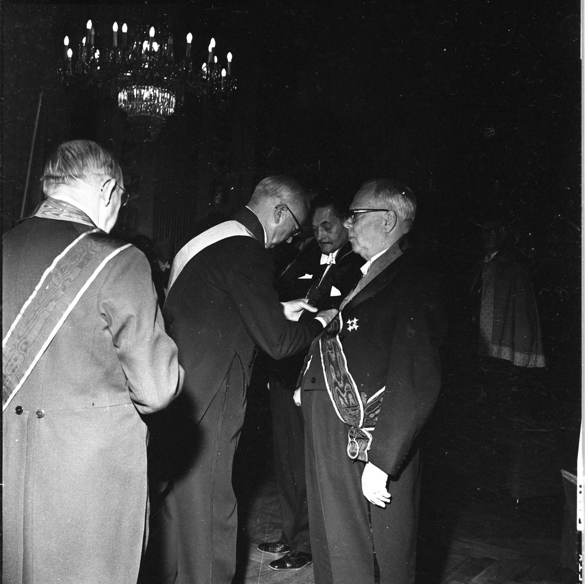 Sällskapet Par Bricole har sammankomst. En man sätter en kraschan på bröstet på en annan man.