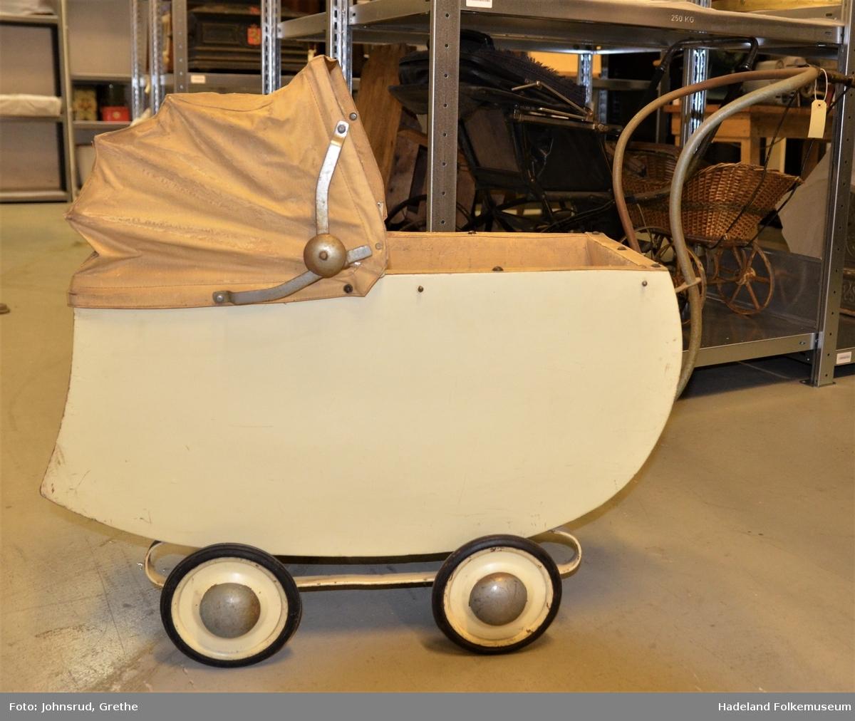 Kalesje med metallspiler, plast på innsiden av bagen, Vogn i finèr, understell i metall, fire hjul med svart gummi, produsentmerke.
