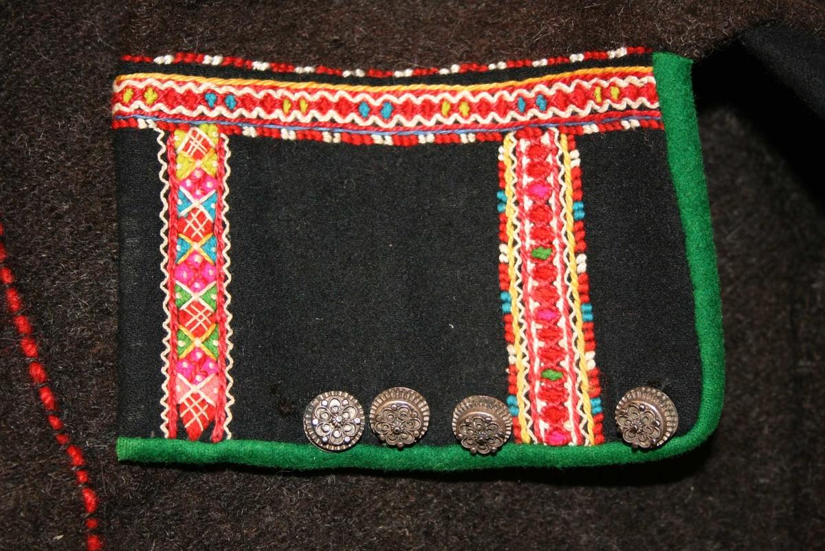 Stutt jakke med lange ermar, broderi og sølvborder. 4 sølvknappar framme.