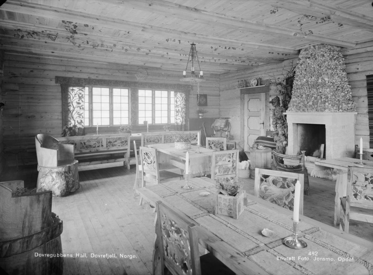 Dovregubbens hall, interiør med utskjærte stoler, kubbestoler, utskjæring rundt vinduene med håndvevde gardiner.