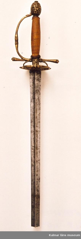 KLM 7197. Värja. Med stukatklinga med etsad dekoration, (blad och blomslingor samt Carl XI:s krönta namnchiffer obs arabiska siffror, avbruten). Fäste gjutet i mässing och förgyllt. svensk officersvärja omkring 1670, en föregångare till den karolinska kommendersvärjan. På parerplåten bladslingor, lejon och enhörning eller häst, i parerstångriktningarna snäckor. Knappen dekorerad som parerplåten. Spolformig i eggriktningarna flat kavel med märken efter metalltrådslindningar, nedtill platt flätning av försilvrad koppartråd. Begravningsvärja. Avbruten symboliskt i samband med begravningen.