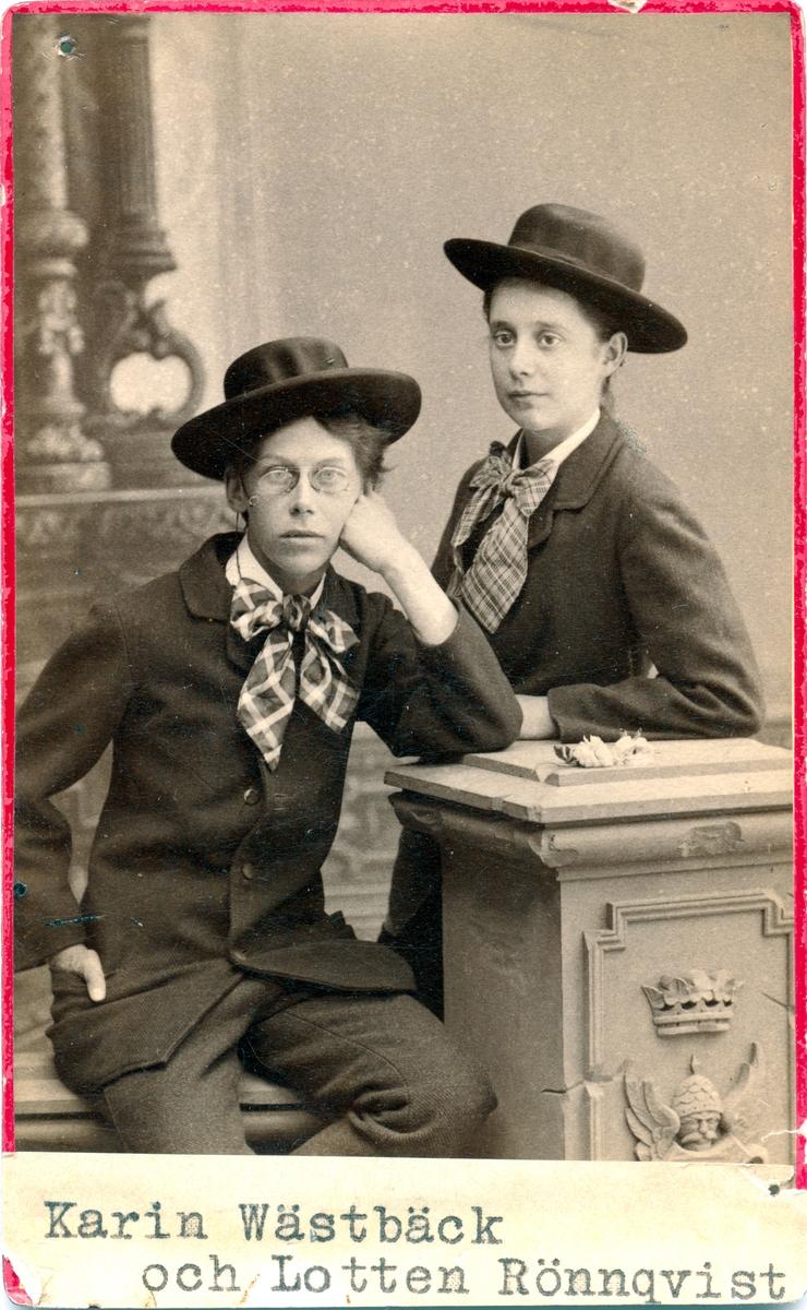 Karin Wästbäck och Lotten Rönnquist i en ateljé, båda har manskläder.