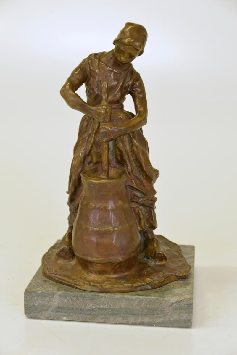 Bronsskulptur av Carl Milles. Står på marmorplatta.