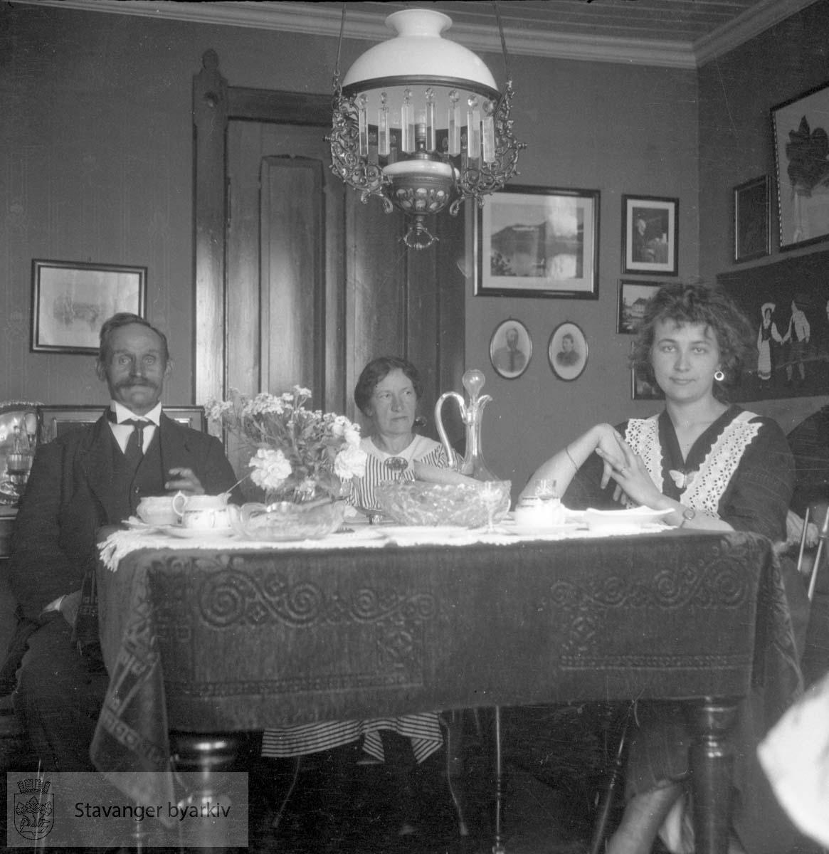 Mann og to kvinner ved spisebord