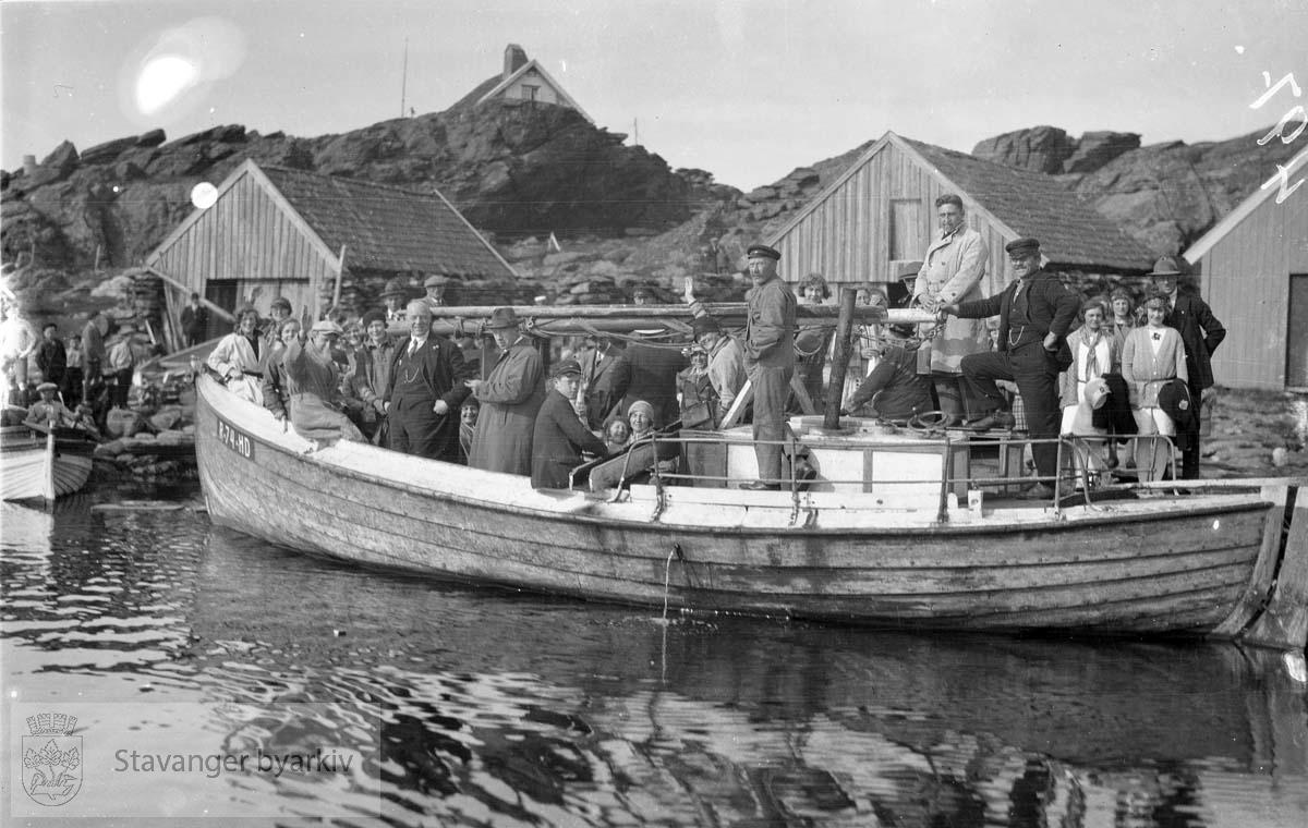 Folk ombord i båt med små naust i bakgrunnen.