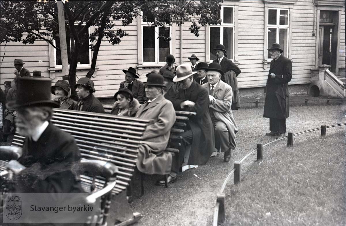 Tilskuere på benker utenfor kommunebiblioteket