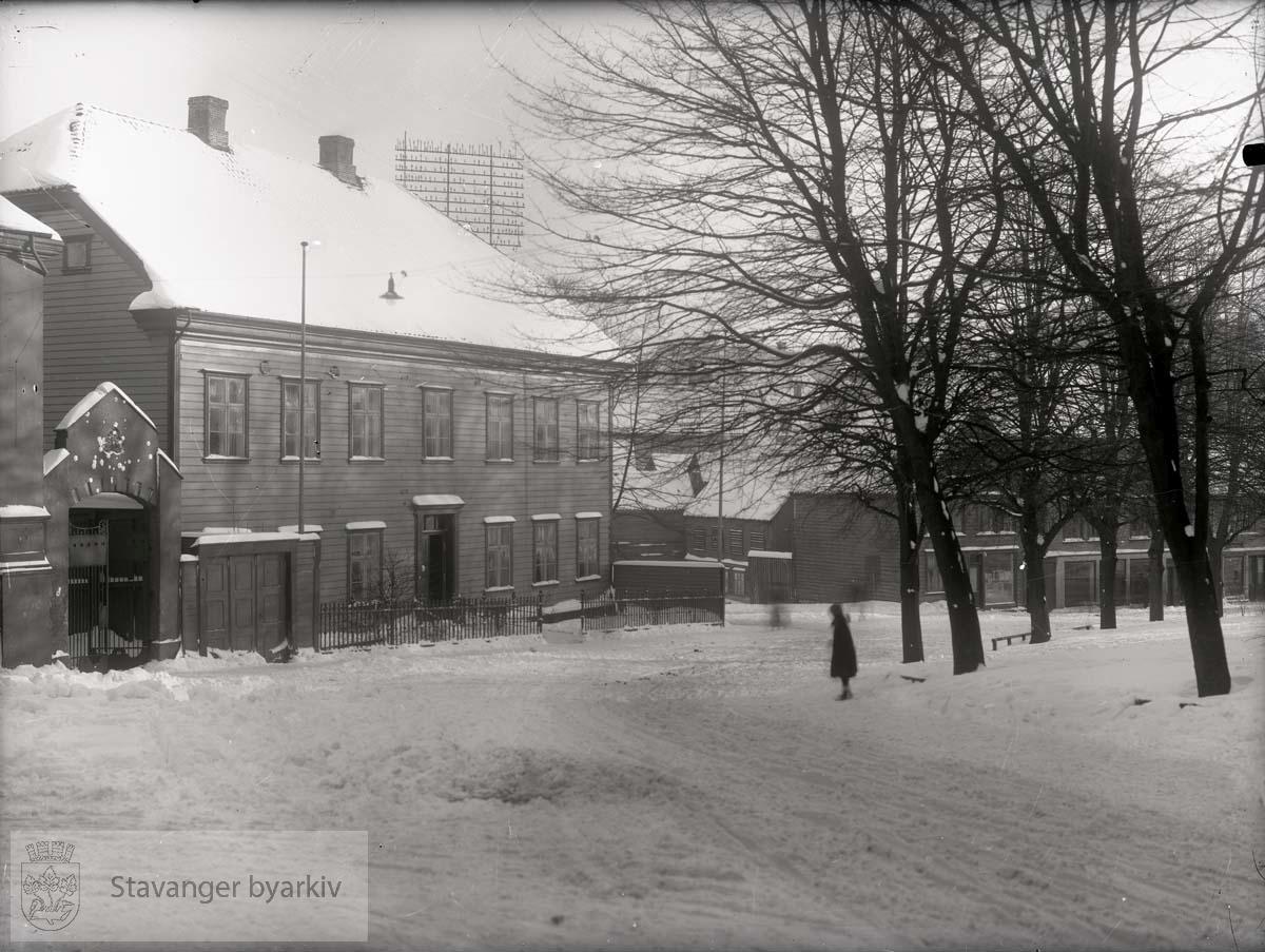 """Tidl. Det Stavangerske Klubbselskap....""""Allerede i 1837 hadde klubselskabet planer oppe om å opføre en bygning i Bispegårdens hage - Klubbhagen - for en sum av 3609 spd. 80 sk., men planen blev utsatt til 1841 og da vilde bygningen kostet 4000 spd. 26. november samme år foreligger en ny meget vidløftig kalkyle på 4 tettskrevne foliosider. Det gjelder nu en større bygning enn tidligere og til et samlet beløp av 5706 spd. 36 skill. Dimensjonene skal være 40 alen lang, 20 alen bred med to tømmeretasjer på gråstens kjelleretasje. Selve tømmerbygningen blir 13 alen høi fra grunntømmeret til gesimsen. Av beløpet var 20 spd. regnet for gatedøren med lås, hengsler, vindu over, trappesten og øvrige forsiringer..Det har ikke vært mulig å finne tiden når arbeidet er begynt, men 10. oktober 1843 optas takst over bygningen som da ikke var ferdig. Den manglet gulver, lofter, dører, vinduer og bordklædning. Dimensjoenen er nu 31 alen lang, 19 alen bred, 12 1/2 alen høi. Taksten blev 1440,0 spd. 26. mars 1845 avholdes ny takst. Nu er huset helt ferdig. Det inneholder 13 tømrede værelser, kjøkken og spiskammer, 3 tømrede ganger, muret kjeller med ildsted, 41 fag vinduer og 8 kakkelovner = 3610 spd. Ved bygningens østre ende står en toetasjes bindingsverk bygning med et gammelt værelse og et ditto skråkammer samt 3 fag vinduer, 5 1/2 alen høi, 12 alen lang og 7 1/2 alen bred = 80 spd. Et plankeverk 95 1/2 alen langt og 3 1/2 alen høit som inneslutter hagen fra gaten = 70 spd. tilsammen 3760 spd., et temmelig avvigende tall fra kalkylen og man må efter dette kunne gå ut fra at det er den første plan der er kommet til endelig utførelse. Senere blev der bygget kjeglebane og kjeglebanehus i hagen på nedre side av Skolebekken med to broer over denne.""""..Fra: Det Stavangerske Klubselskab og Stavanger by i 150 år. Stavanger 1934. Forfatter: Trygve Wyller."""