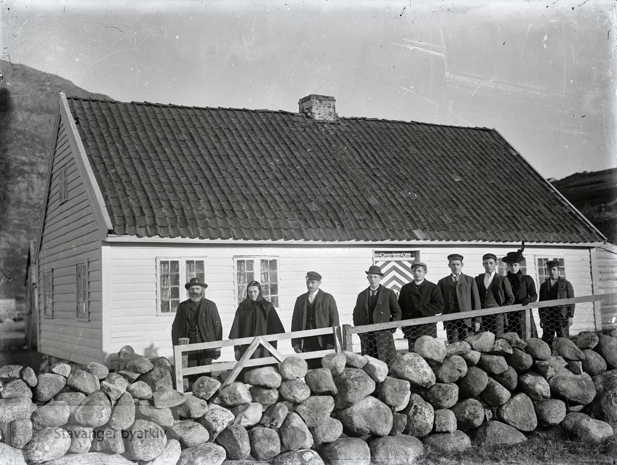 Gruppe mennesker ved steingard foran hus på landet