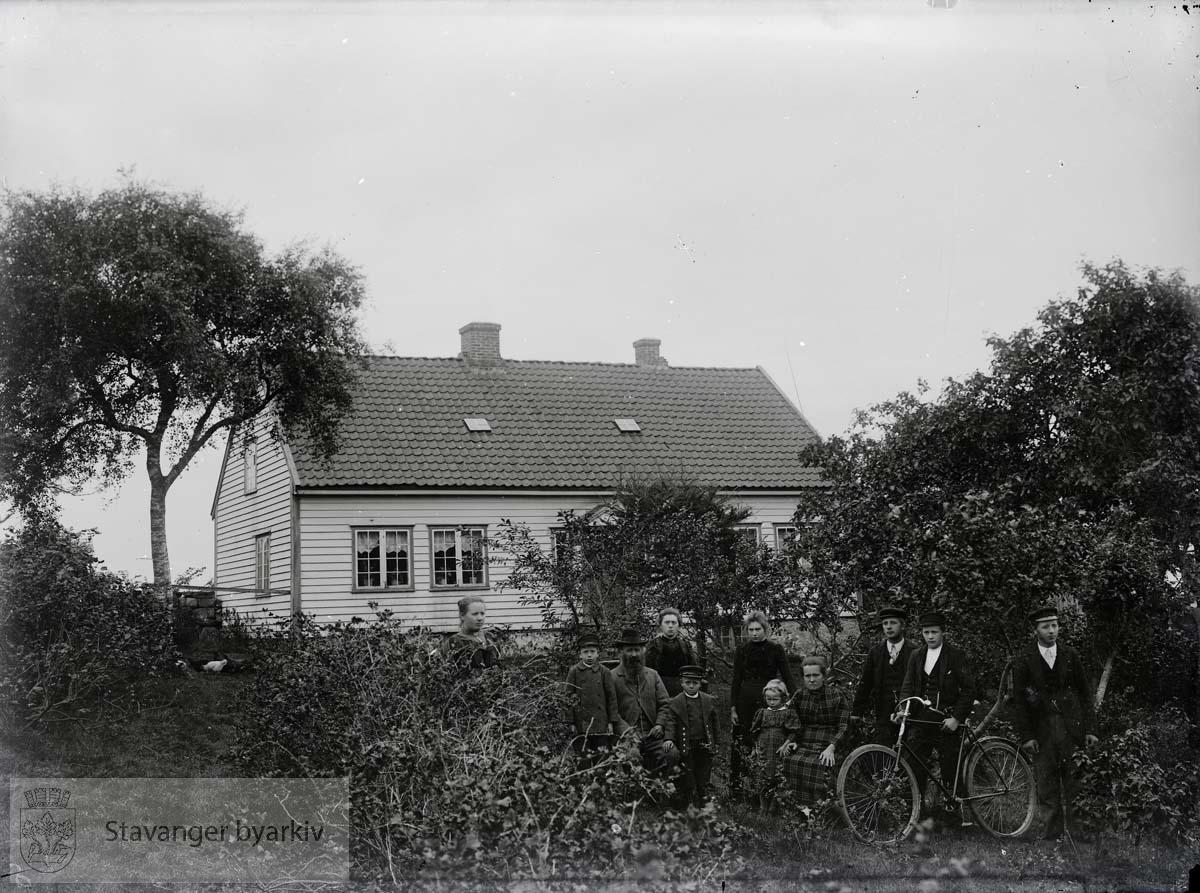 Gruppe mennesker med sykkel foran hus på landet