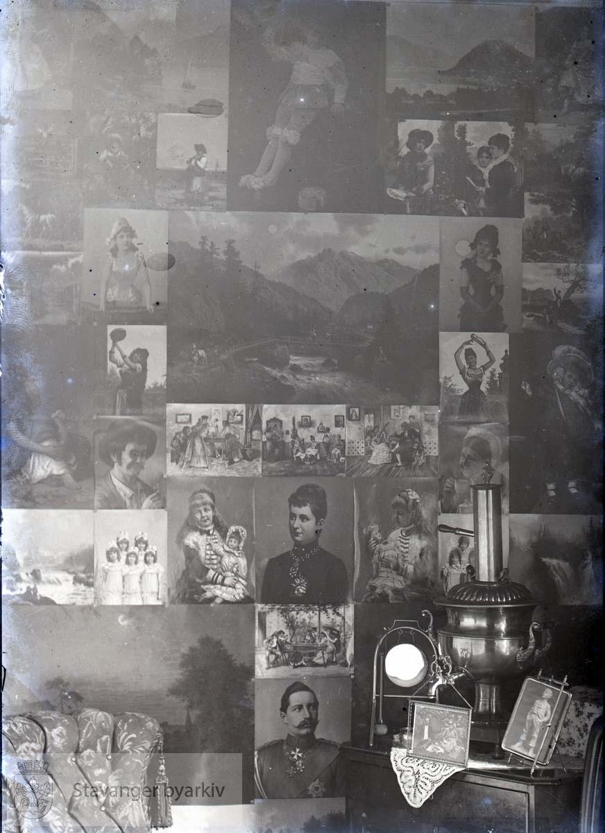 Til høyre en samovar. Veggen tapetsert med bilder fra magasiner....