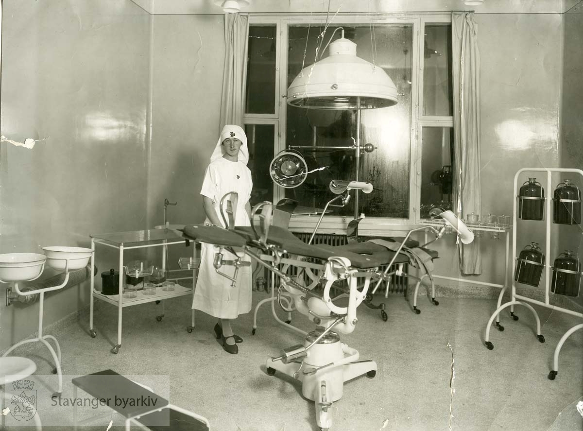 Sykepleier på gynekologisk avdeling. Gynekologstol i midten av bildet. Annet utstyr og apparater rundt om i rommet. .Avlevert av Harald Bjørnestad.