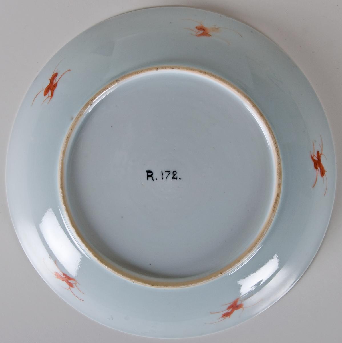 Riskoppar/ tallriksform, porslin. 4 st. kupiga. Mörkblå glasyr med övermålning i guld, lansdkap och ornamental bård. Vit glasyrundertilloch på brämets undersida. Undertill fem växtornament i orangefärg. Utan fabrikationsmärke. Kina, Powdered Blue.