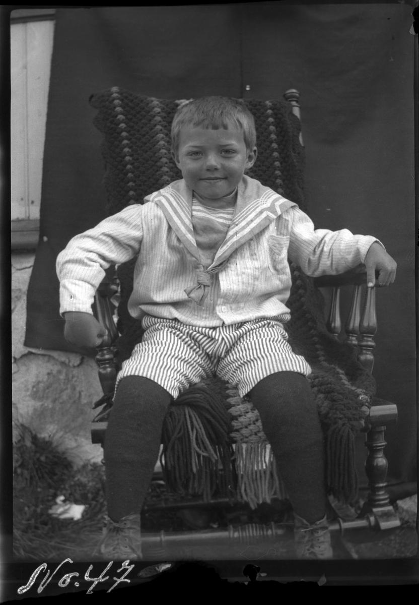 Portrett av en gutt i en gyngestol, fotografert ute foran et opphengt teppe..