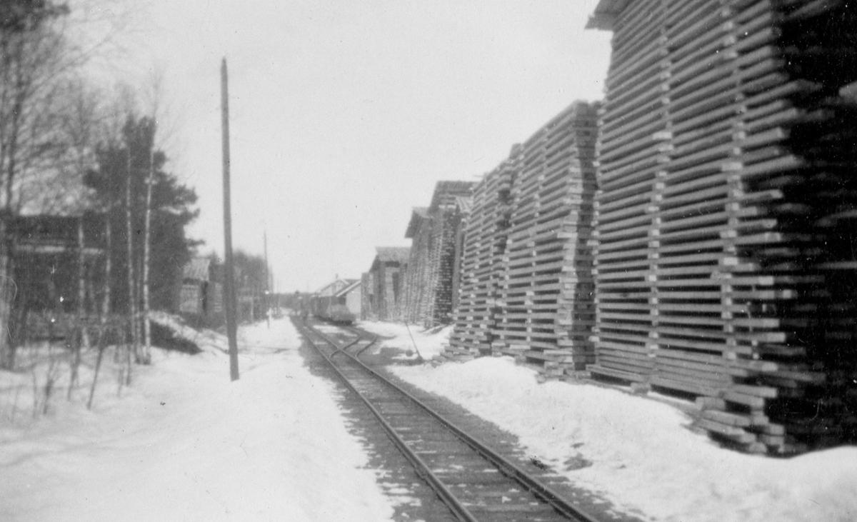 Ved- og plankelagre venter på transport, trolig under krisen i 1918.