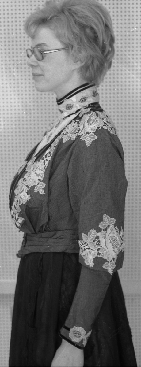 Ripsband med mønster i livet med innskrift Gina Andersen Moen.  Utfyllend beskrivelse i kort kartoteket.