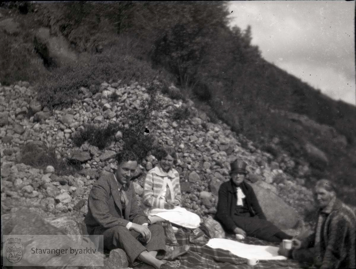L. Storhaug og tre kvinner sitter på teppe foran ur