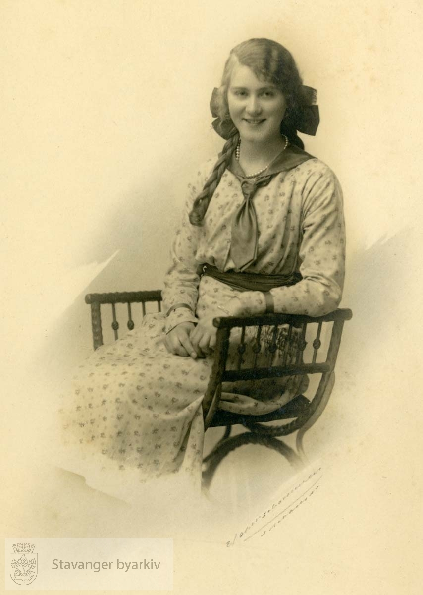 Portrett av ung pike som sitter i en stol