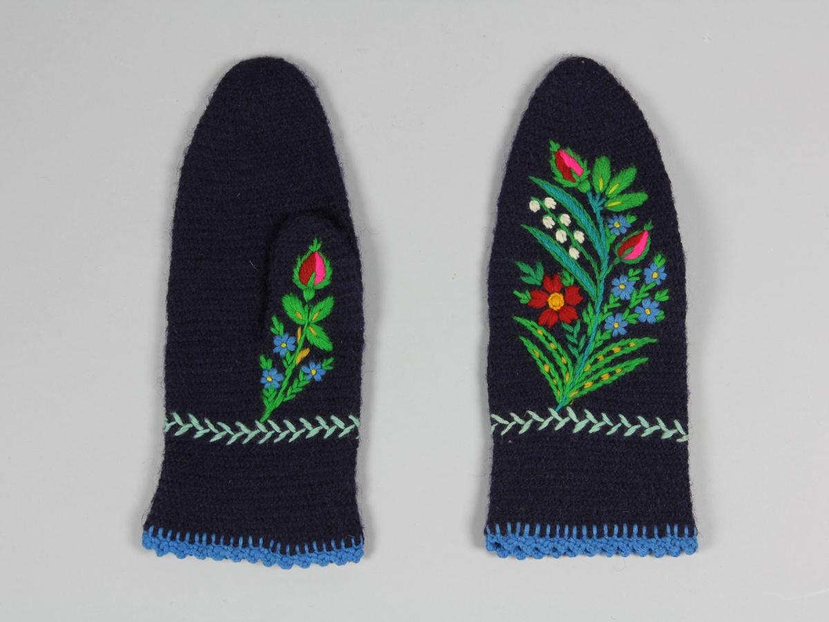 Ett par tumvantar nålbundna av mörklblått ullgarn. Med färggranna blomsterbroderier på ovansidorna och tummarna. Längs kanten en virkad uddkant i ljusblå ull.