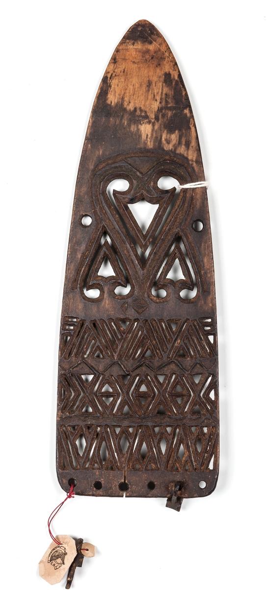 Stryksticka av trä, platt skiva med tvär ända, avrundad och spetsig i andra änden. Utskuren med genombrutna mönster. I hål utmed tväränden hänger två små klossar av trä, troligen saknas 4 stycken. Längd 21 cm, bredd 7 cm.
