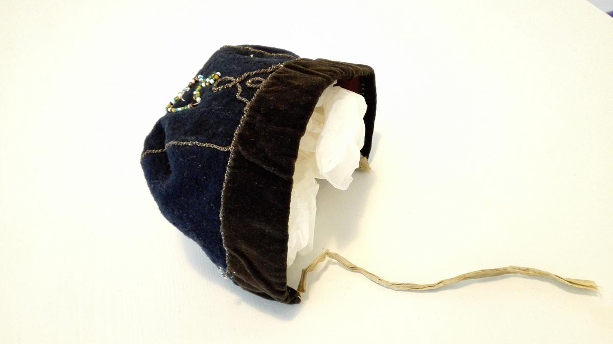 1 kindbeinshue.  Kindbeinshue av blaat vadmel, kantet med sort flöiel, utsydd med sölvsnorer og hjerteformet perlebroderi, foret med brunt - nu mölspist - töi.  Kjöpt av gaardbruker Kristen Flæte, Framfjorden.