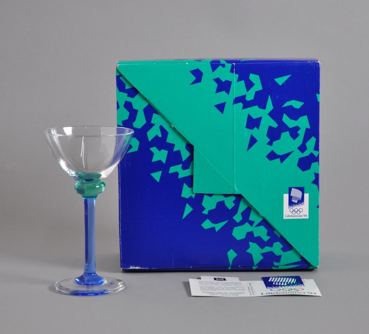 Likørglass med blått stett med fakkelmann, turkis kant like under glasset. Glasset ligger i original emballasje.