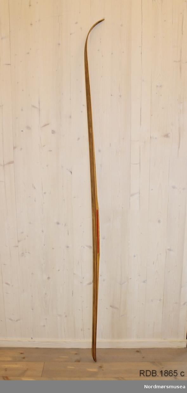 Tilnærmet jevnbred ski med liten bue. Bøy uten tupp. Avrundet bakende med litt oppbøy. Dekorert med ei brun stripe på trehvit bunn.