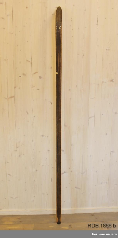 Avsmalende, jevnbred ski med liten bue. Bøy uten tupp. Avrundet bakende med litt oppbøy. Grønn Skigum hælstøtte. Dekorert med ei brun stripe på trehvit bunn.  Stempel og klistremerker på skiet.