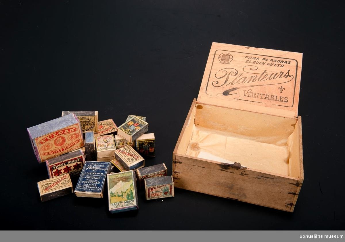 30 tändsticksaskar (tomma) av olika format samlade i en cigarrlåda av balsaträ. 11 olika etiketter från följande identifierbara tillverkare: Uddevalla tändsticksfabrik Jönköpings Westra tändsticksfabrik Vulkan tändsticksfabrik, Tidaholm  Cigarrlåda med tryckt  text på lockets ovan- och baksida: PARA PERSONAS DE BUEN GUSTO Planteurs VERITABLE  Ur handskrivna katalogen 1957-1958: Tändsticksaskar 30? askar av 12 olika märken  Lappkatalog: 90