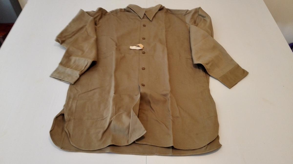Form: Rett skjorte m/lite dobbelt berestk. Runda skjorteflak med liten kile i sidene, skjortekrage med  spisse snippar. Isydde ermer med enkel splitt og mansjett. Knapping framme med 6 knappar på høgre og tilsvarande knapphol på venstre framstykke.