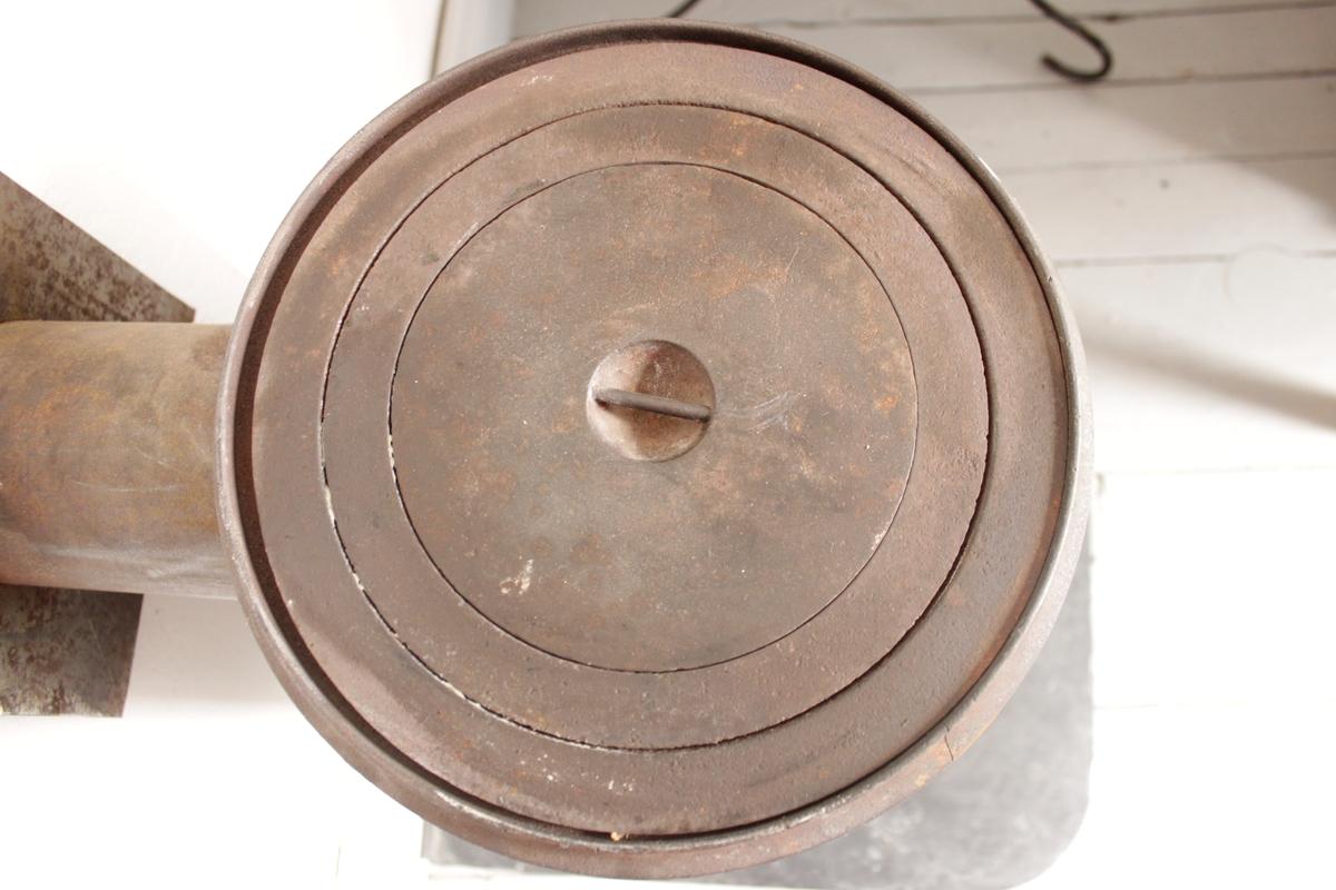 Cylindrisk gjutjärnskamin stående på fyra svängda ben. Spisluckan är placerad högt upp på cylindern och ovanpå finns ett rikt dekorerat lock. Under locket finns en kokplatta. Rökgången går in i väggen. Kaminen står fritt en bit från väggen. Dekorationerna består av stiliserade mönster.