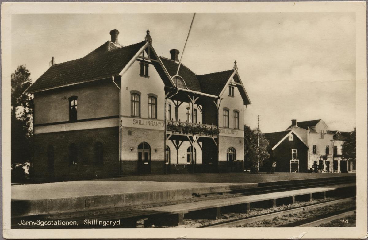 Spårsida av station med vy på stationshus och perrong.