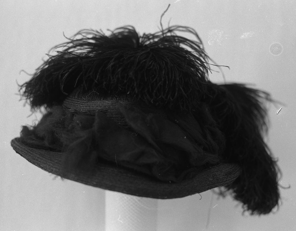 Hatten har en 5, 5 cm. brem. Rund pull. Hatten er flettet av et bastlignende fiber. Bremmen holdes i fasong av en ståltråd langs ytterkant, og en mindre ståltråd ved overgang fra bremmen til pullen. Pullen er omvindet av flere lag svart flor (tyll?), 4 fjær (strutsefjær?) festet bak på hatten hvorav to er lagt i sving fremover pullen, en svinger til siden og en er bøyd bakover. Pullen er stivet opp innvendig med stiv, grov gaze.