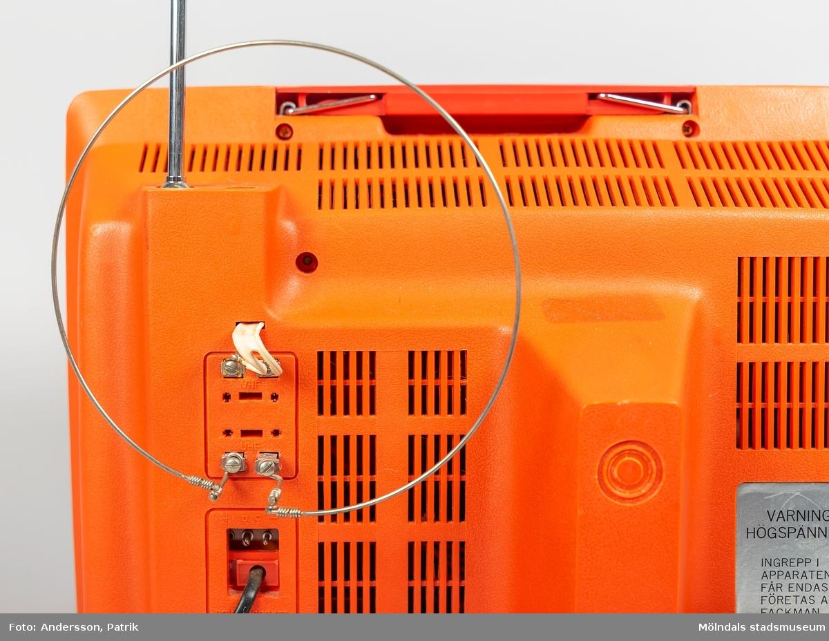 Liten röd bärbar tv med 11 tums skärm av märket ALEX. Tillverkad under 1970-talet. Apparatens ytterhölje är av röd plast. Den har två större vred på vänster sida om skärmen, att välja tv-kanal med. Samt tre mindre vred att ställa in ljus, kontrast och volym med. På ovansidan finns ett utfällbart handtag att bära TV:n med.
