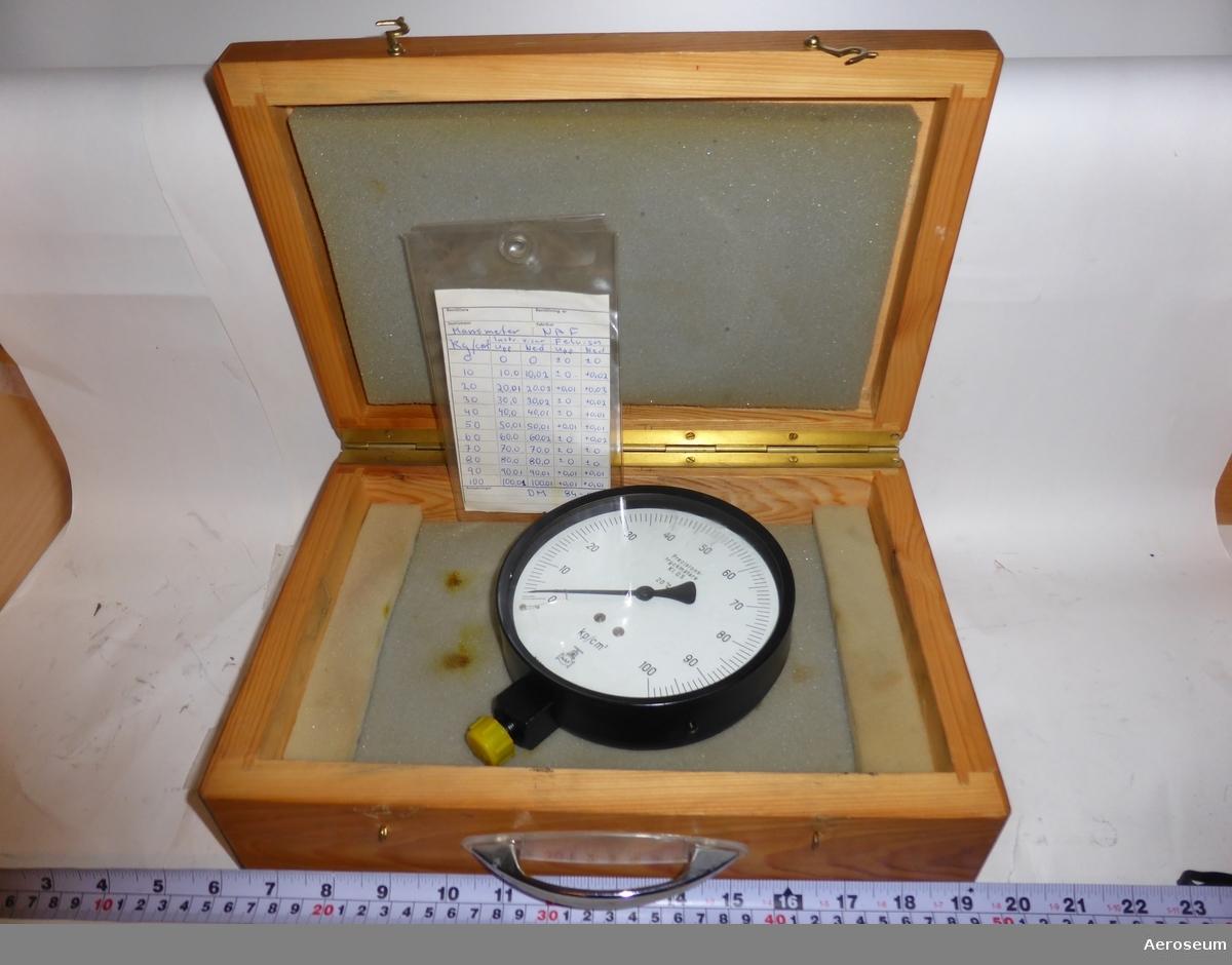 """En precisionstryckmätare (kallas även manometer) i en lackad trälåda. Tillverkad av NAF, märkt med """"2 Hkp div 84-04-T"""". Ett instrumentprotokoll på en papperslapp i plastficka medföljer."""