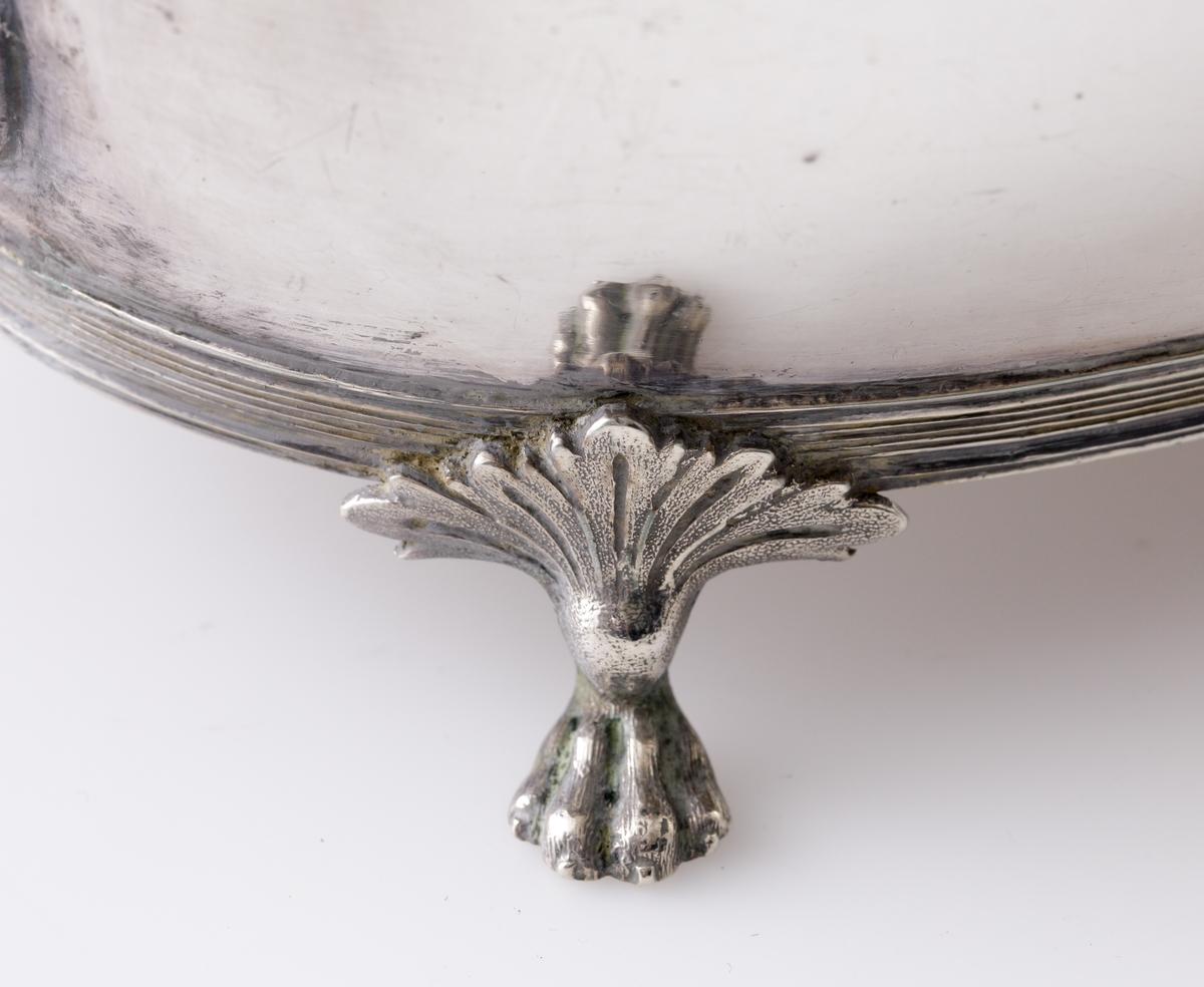 Tekanna av silver.  Oval modell på fyra tassfötter med palmettdekor. På livet en lejonmaskaron på båda sidor. Välvt lock med gjuten dekor av vinblad och vindruvor. Svarvad, svärtad träknopp. Svärtat uppsvängt handtag av trä. Stämplar på undersidan av kannan.