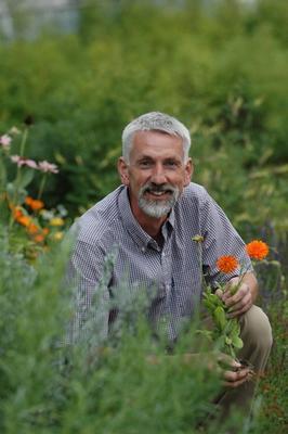 Fargeprotrett av Gunnar Fossaa som sitter i gresset med oransje og hvite blomster rundt seg.