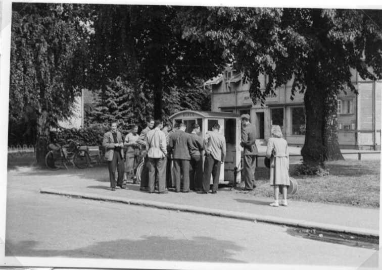 Ett antal män stående vid en glasskiosk på okänd ort. Till höger en militär uniform och en kvinna. I bakgrunden ett trähus med skylt om blanda annat Bok- och pappershandel.