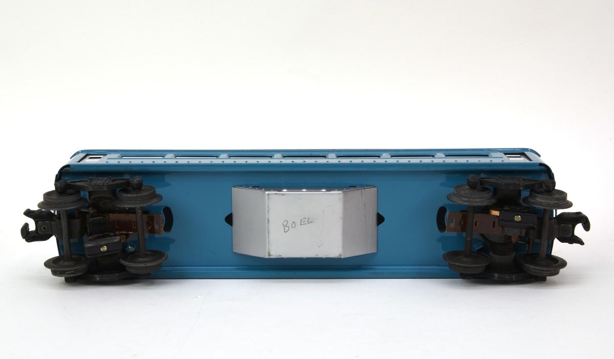 """Personvagn av plåt med boggier och elektriska vagnskopplingar (:7). Vagnen är blå med tak, dörrar och fönster i silver. Fönstren är täckta med en lätt frostad plastremsa och vagnen saknar inredning. På sidorna under fönsterraderna finns """"2430"""" och """"PULLMAN"""" tryckt i silver. Taket är fäst med en skruvad klammer i korgen som är pressad ur ett plåtstycke. Boggierna är vridbara och har varsin liten strömupptagare för att aktivera den elektromagnetiska vagnkopplingen.  Till vagnen hör en förvaringsask i kartong (:8) med tillverkarnamn och modellnummer tryckt i blått mot orange botten."""