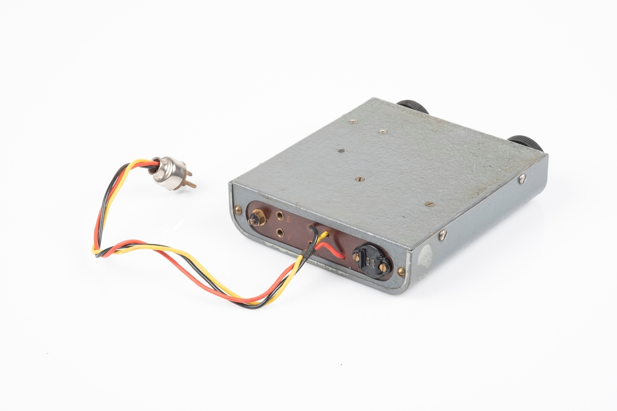 En kortbølgeradio med ytterplater av metall som er lakkert i grått. Radioen har to svarte vriknapper. Det er et lite vindue ved den ene vriknappen som viser frekvensen. På baksiden er det ledning som kobles til batteriet. Det er to hull til plugger og en kontakt for øreproppene. Det er påfestet en plate med instrukser på på oversiden. Mellom vriknappene er det påfestet en liten plate med modellnummer.
