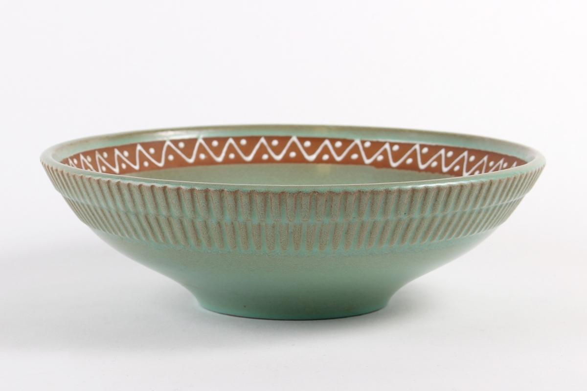 Skål som innvendig er dekorert med et uglasert felt langs kant med pyntebord. Utvendig med riflet dekor.