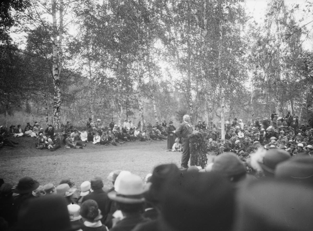 Mann holder tale foran en større forsamling, friluftsarrangement
