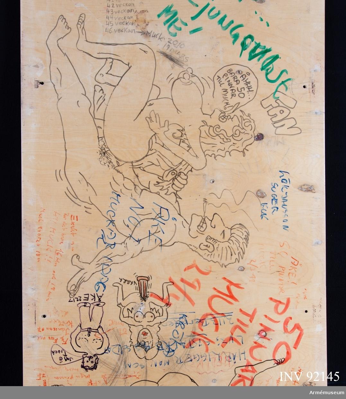 Sängbotten i trä avsedd för våningssäng i metall. Nedklottrad med text och bilder av mestadels sexistisk karaktär. Flera personer har använt ytan för att räkna ned veckorna och dagarna fram till muck.
