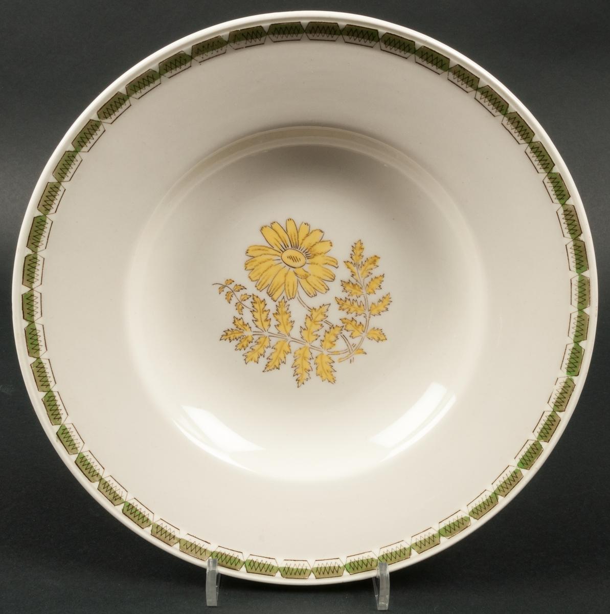 Tallrik dekor Pyretrum. Koppargravyr med lavering i gult och grönt. Dekoren föreställer en prästkrage eller liknande blomma.