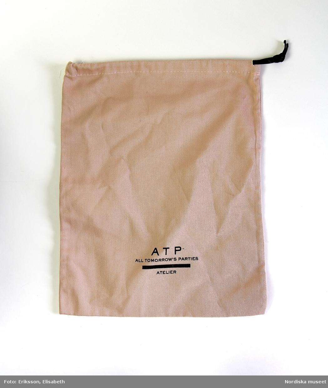 a: Axelväska av svart skinn med oreglerbar axelrem fästad i bred hälla upptill på väskans ena sida, axelremmens andra sida är fastsydd vid motsatt sidas kant. Väskans sidostycken vart och ett i två delar, skurna och sammanfogade i böjd form,  kännetecknande för flera av ATP Ateliers väskmodeller. Rektangulär botten av läder, ficka på insidan med dragkedja av gulmetall och dragtapp av svart läder. Väskans pris i butik 2019-01-28 ca. 4000 Skr. b: Tygpåse av ljust beige kypertvävt tyg, dragsko upptill med snodd att fästa vid hälla på väskans insida, på hällan kraftig tryckknapp i gulmetall.   Etikett av benvit papp med tryckt brun text: ATP ALL TOMORROW'S PARTIES ATELIER MADE IN ITALY, fästad med brunt band runt samma hälla  som tygpåsen (b). Bilaga samt skannad kopia.  Informationsblad, vikt, i innerfickan. Bilaga samt skannad kopia. /Helena Lindroth 2019-01-28