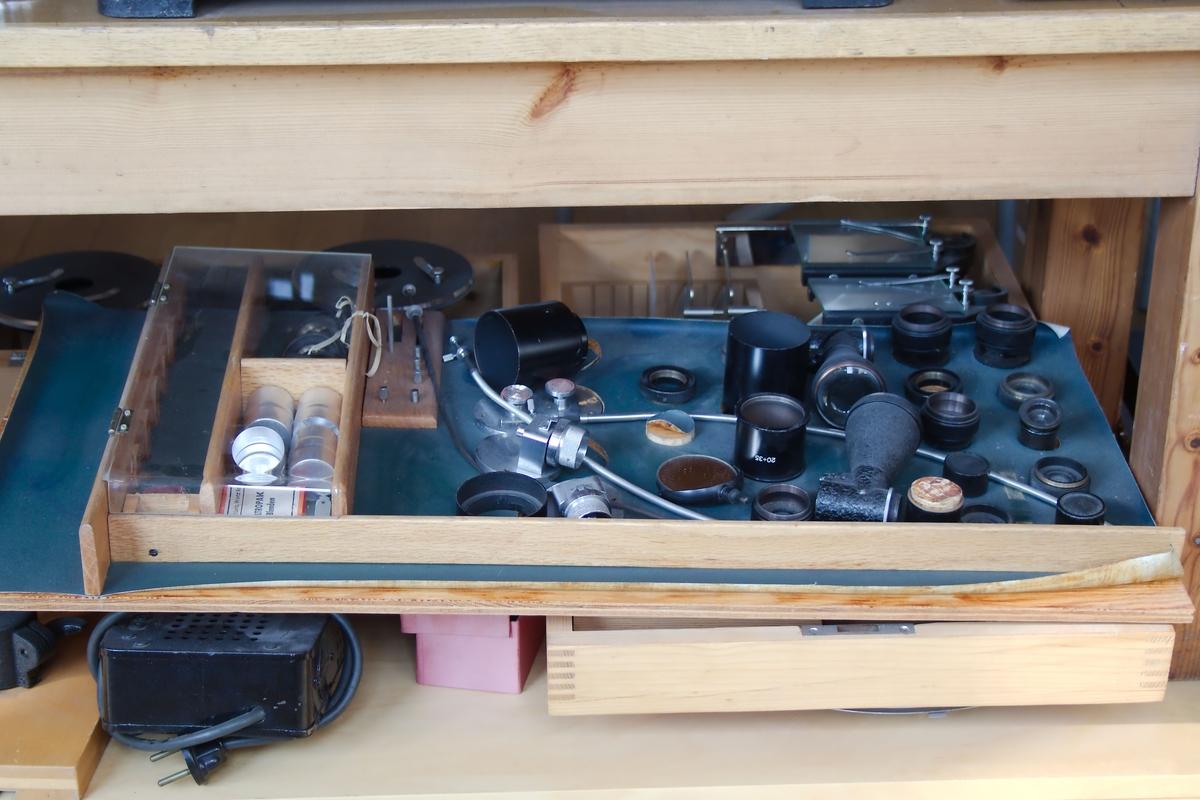 Sammenligningsmikroskop i mange deler. Mikroskopet har fotoenhet, lysmåler og belysningkilde samt ekstra bro med okularholder og objektivholdere med speil.
