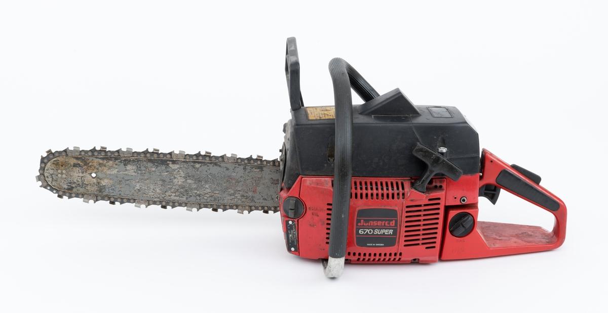 """Motorsag av typen Jonsered 670 Super med påmontert sverd og sagkjede. For registrator virker saga å være tilnæremet komplett, mangler en mutter i sverd-/kjededeksel. Motorsag av denne typen er særlig egnet til arbeid med grov skog og harde treslag.   Sidedeksler, toppdeksler, starthus, hendler og en rekke andre komponeter er laget i hard plast. Saga er blant annet utstyrt med elektronisk tenning, avvibrerte håndtak, vernebøyle, varme i håndtakene, automatisk kastbegrensende kjedebrems, justerbar automatisk  oljepumpe. Fremre håndtaksbøyle er polstret med svart gummi.  Oljepåfyllingen er plasert på venstre side, fremme på motorkroppen. Drivstoffpåfyllingen gjenfinnes på venstre side, bak på motorkroppen.   Kjedebremsen og vernebøylen er montert i samme enhet som sverd-/kjededeksel, ved å skru av festemuttrene til dekselet følger kjedebremes og vernebøyle med.    Det gjengis her noen tekniske spesifikasjoner fra omtalen av Jonsered 670 i Jobus skogskatalog: (For en allmenn beskrivelse av sagas spesifikasjoner, se vedlagt fil under fanen referanser. Her gjenfinnes en skannet versjon av omtalen av saga i Jobus skogskatalog)  Sylindervolum/slagvolum: 66,8 kubikkcentimeter. Effekt: 3,3 kW.  Oljetank: 0,45 liter. Divstofftank: 0,73 liter. Vekt: 7,2 kg (inkludert 15"""" sverd og kjede)."""