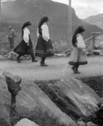 Tre jenter i setesdalsbunad på en veg