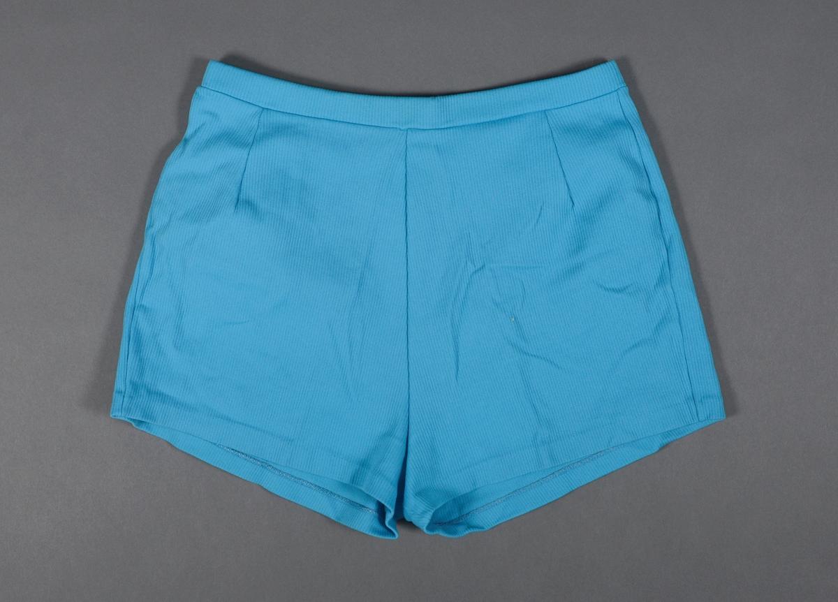 En badeshorts/shorts laget av nylon. Stoffet er blått og det er vevde striper i stoffet. I livet er det strikk. Det er sydd to legg både foran og bak. På innsiden er det sydd på merkelapper med produktinformasjon og størrelse. Badeshortsen er i størrelse 44.