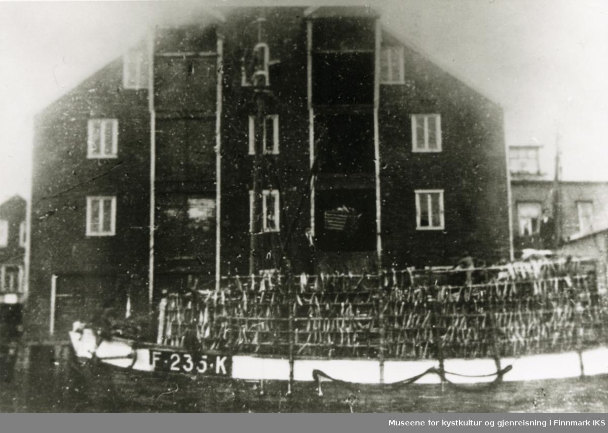 """Honningsvåg. Fiskebruk og tørrfisklager til Richard Floer AS på Holmen i """"Tyskerbrygga"""". Foran Mj """"Freya"""" med tørrfisk på hjeller. 1930-tallet."""
